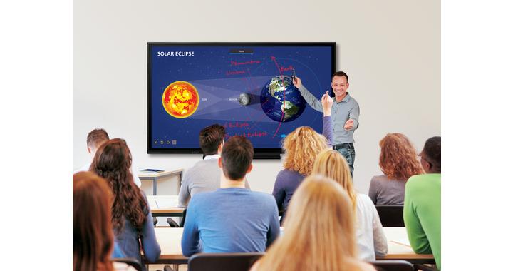 Alumnos adultos mirando al profesor y a la pizarra interactiva